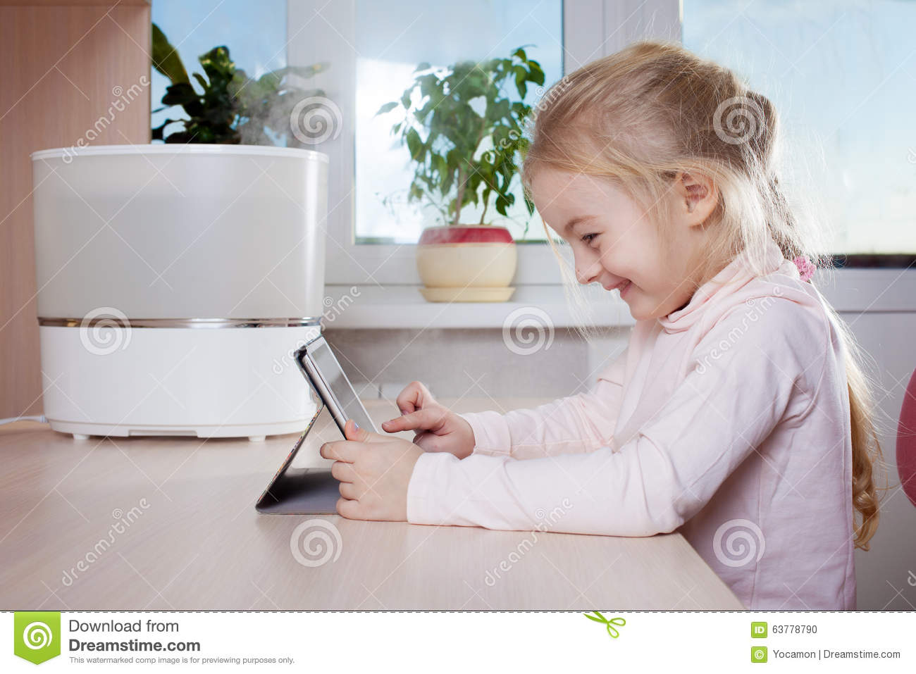 Photo: Little girl with tablet pc sitting near humidifier and smiling #3E6F8D