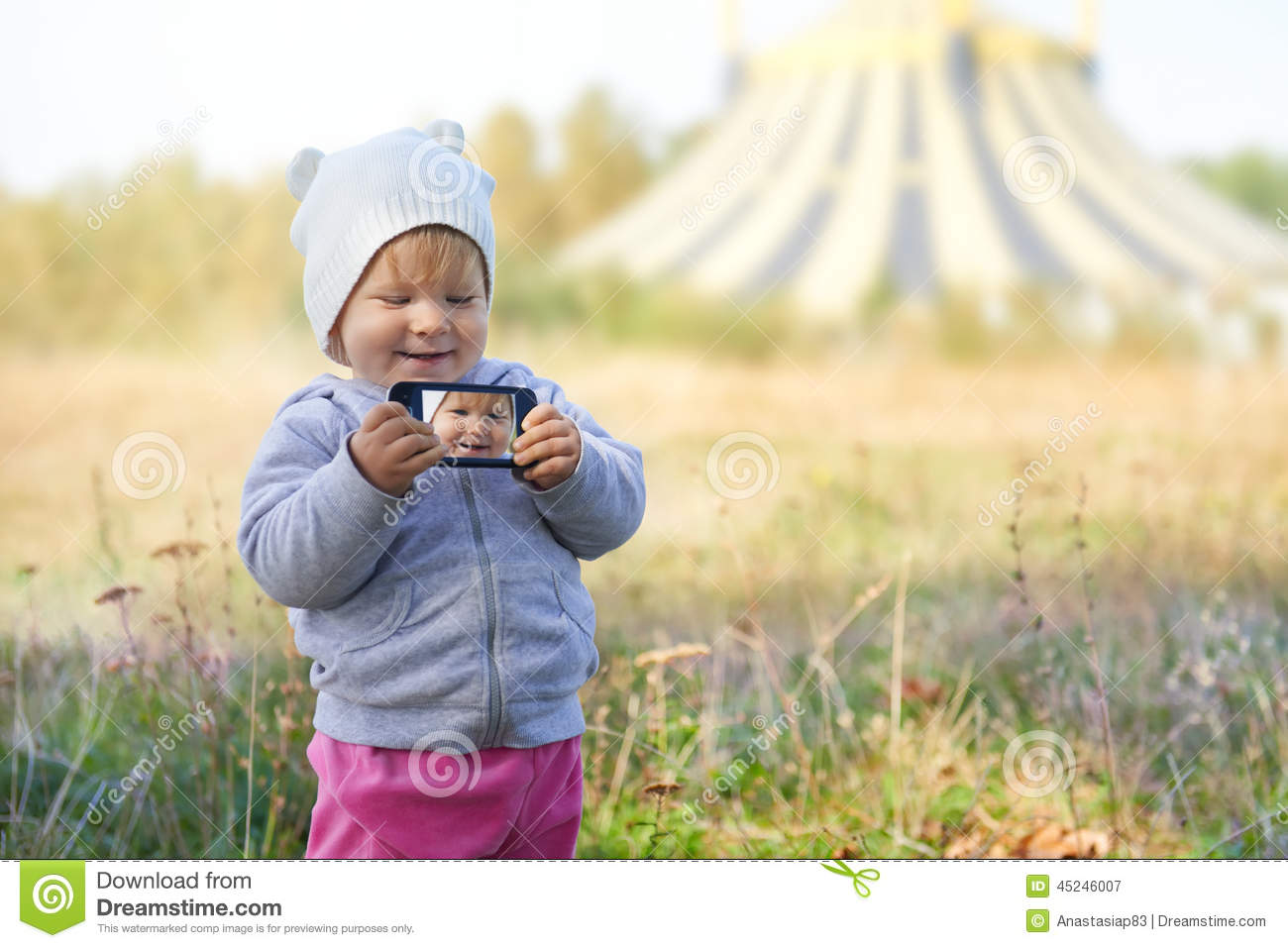 Little girl taking selfie near the circus