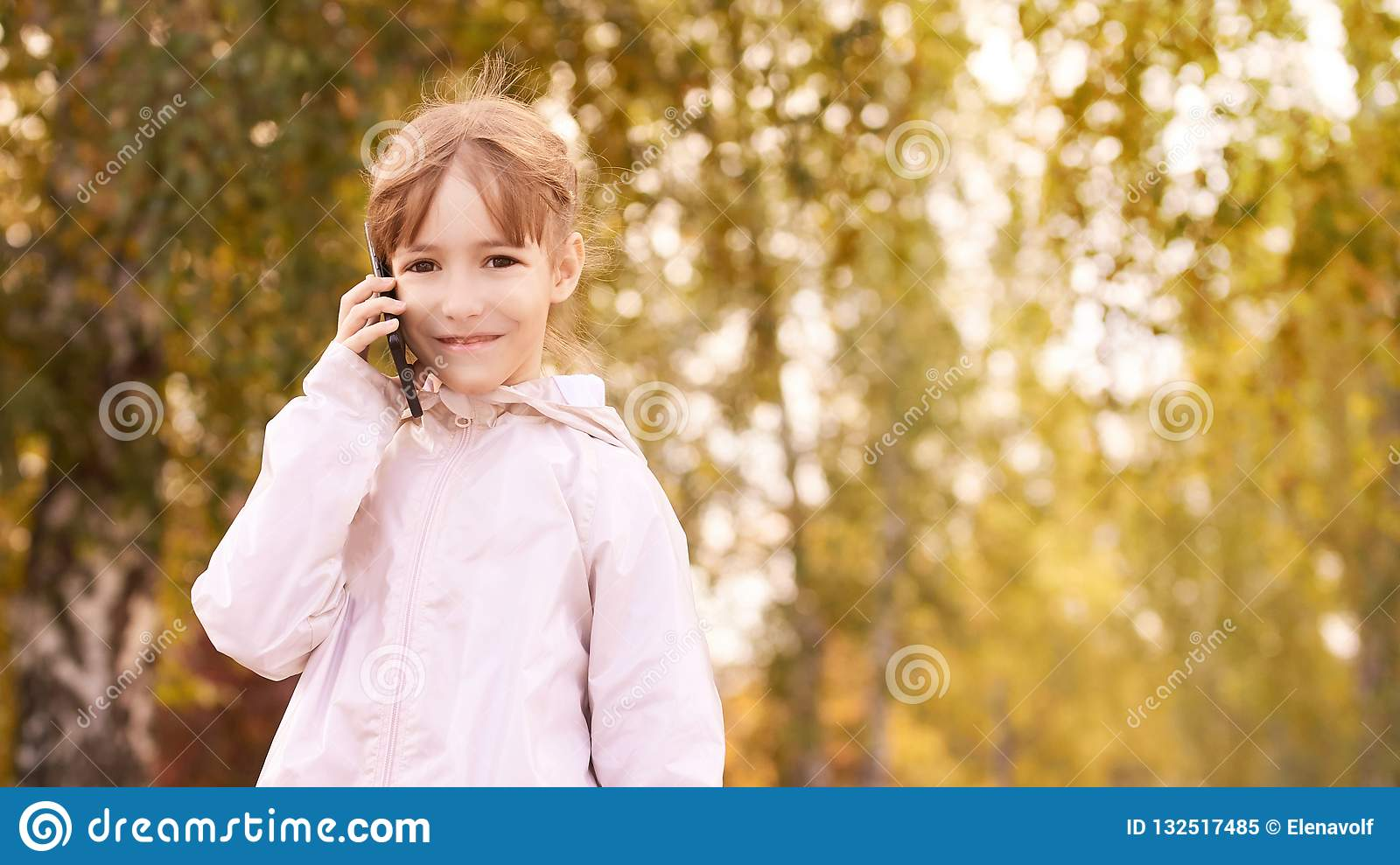 Little girl talk phone. Autumn background