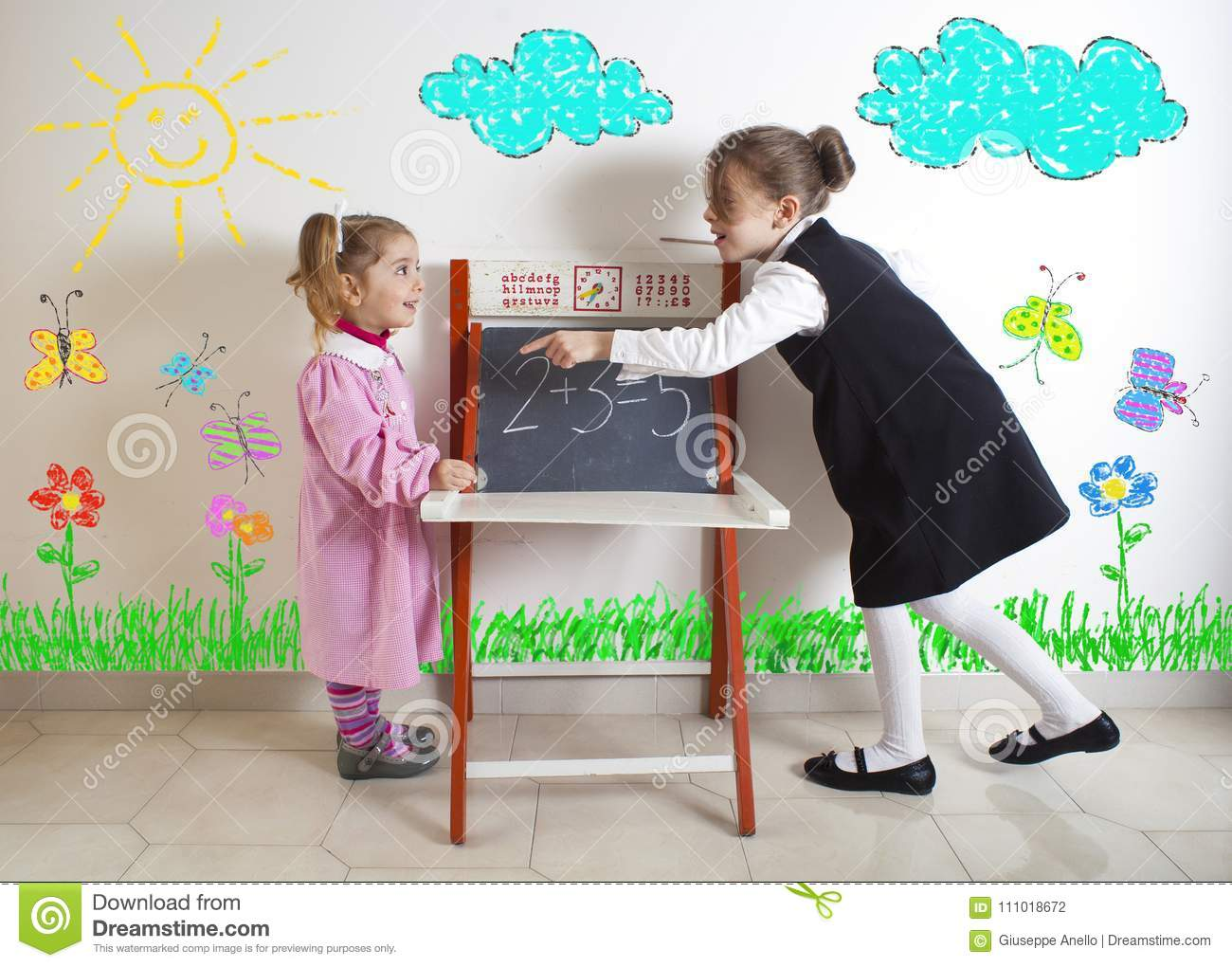 Little girl teaching mathematics to a younger child