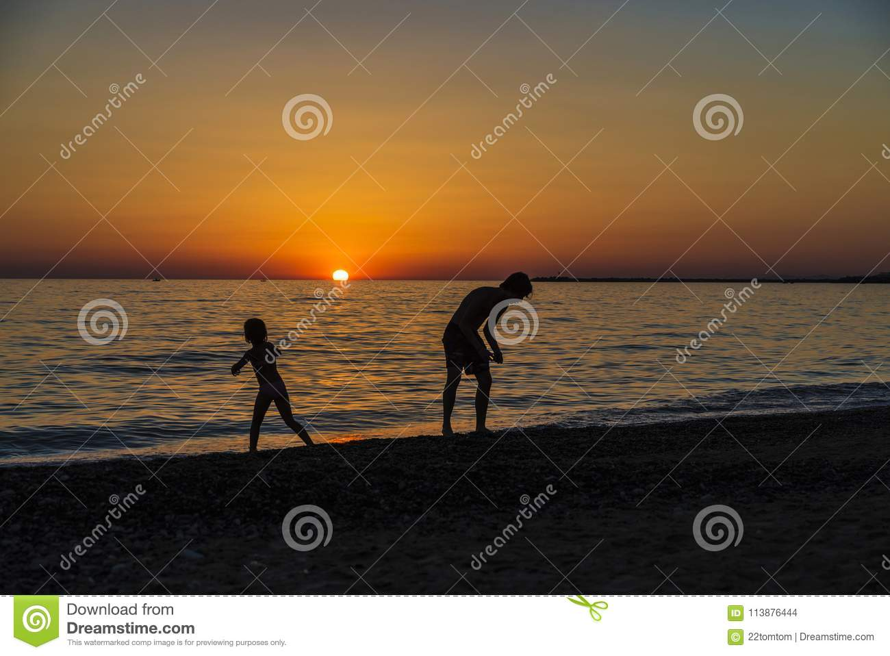 Little girl and teenager playing on a beach at sunset