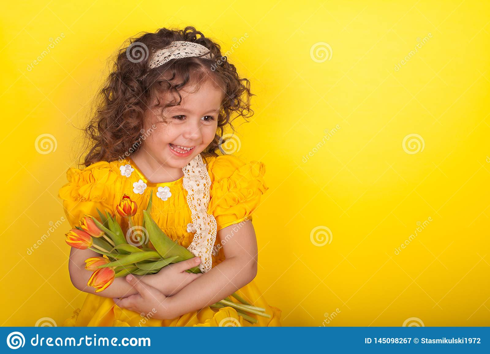 Little girl with tulips in hands on yellow background