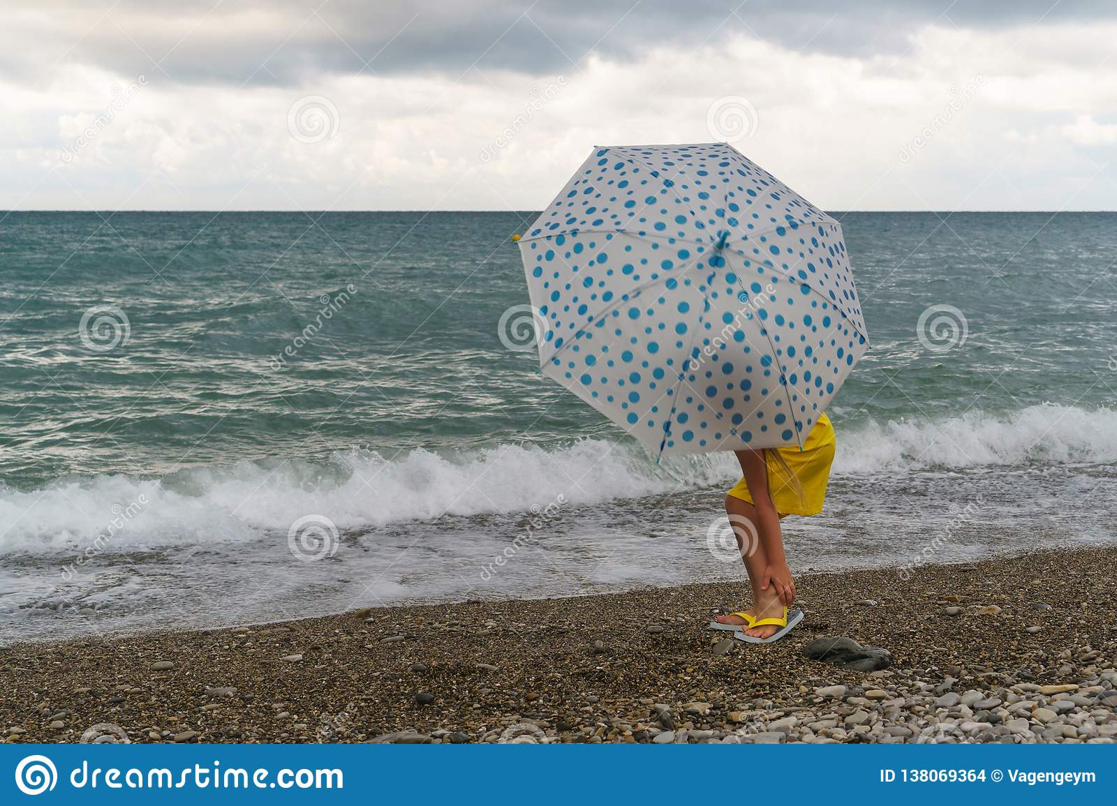 Little girl with umbrella on beach in bad weather