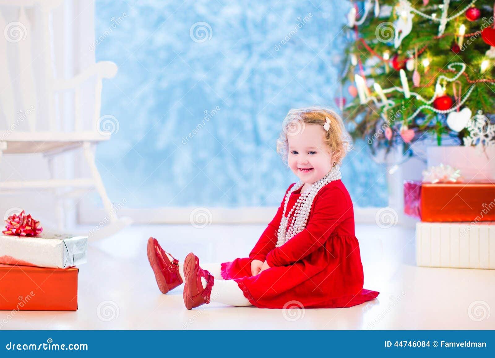 Little Girl Under Christmas Tree Stock Photo