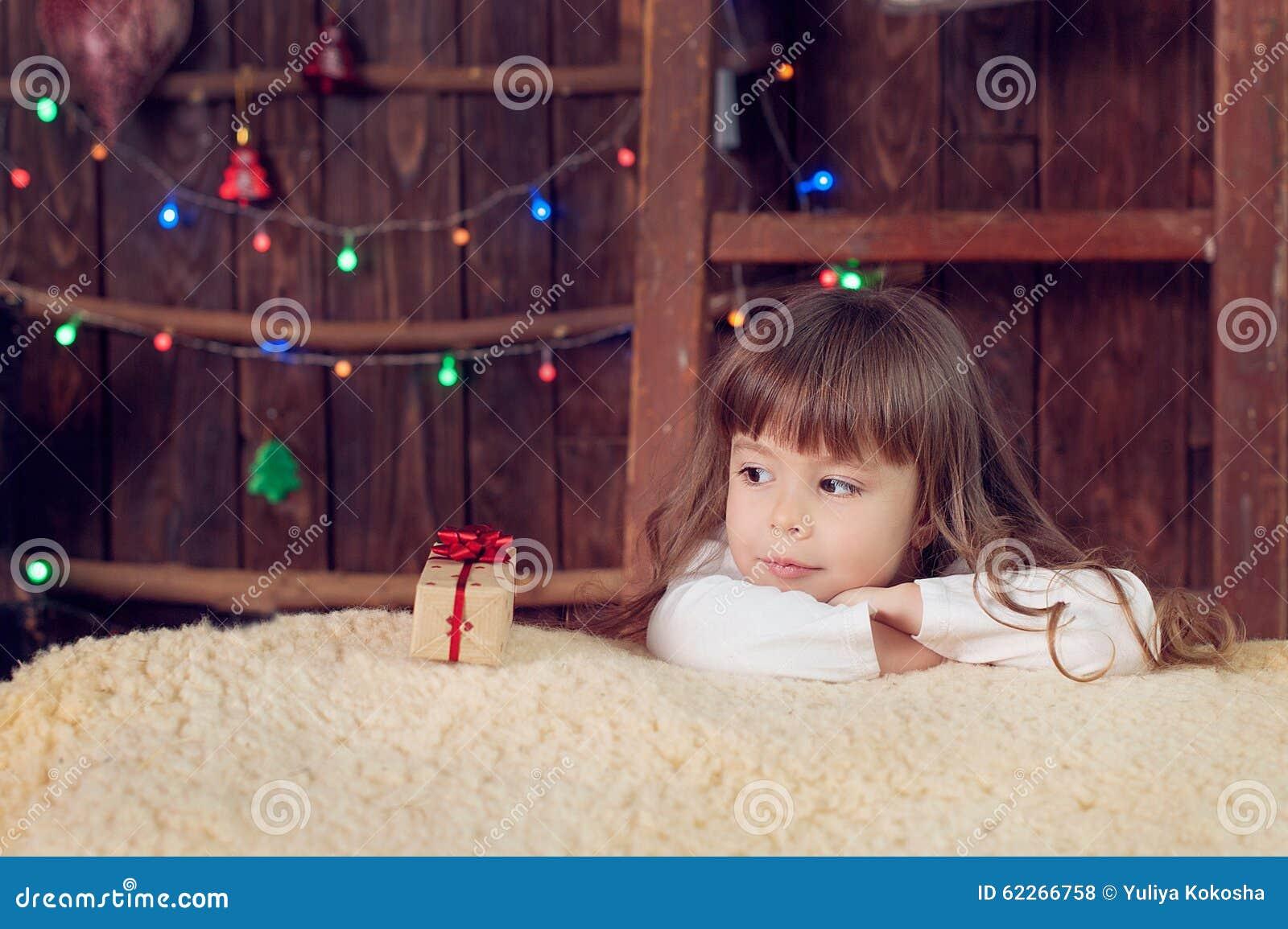 Little Girl Under The Tree On Christmas Stock Photo