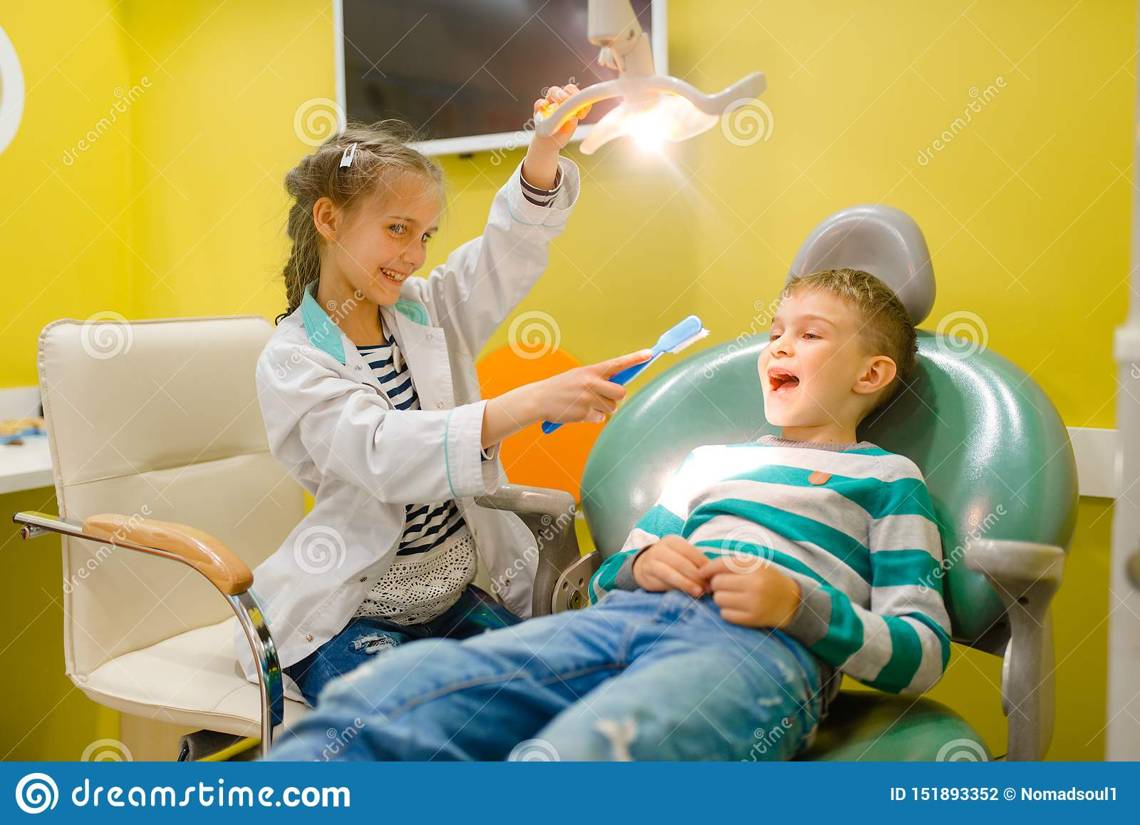 Little girl in uniform playing dentist, playroom
