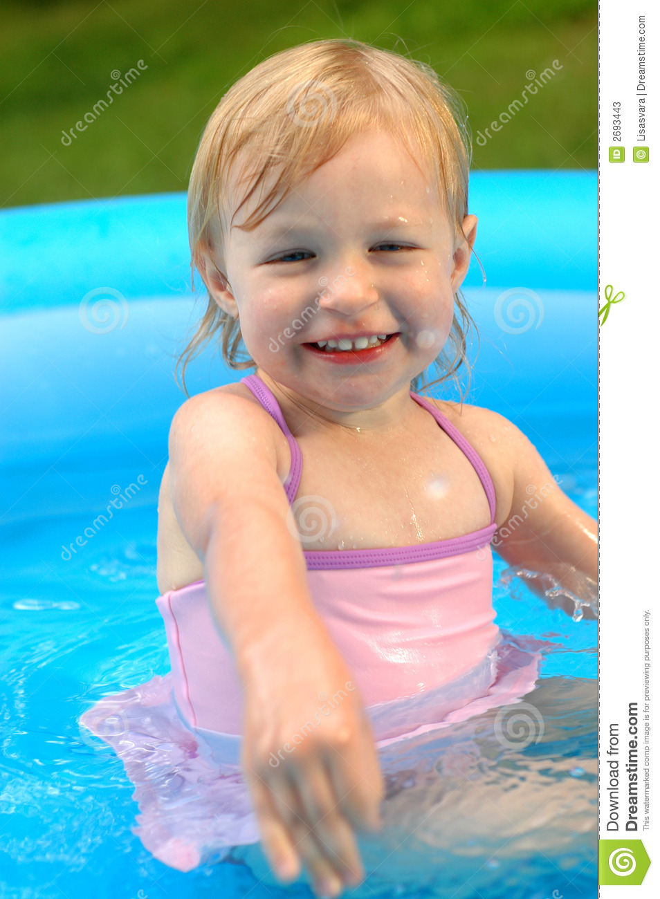 ... almost 3 years old) outside in a wading pool, wearing a pink swimsuit