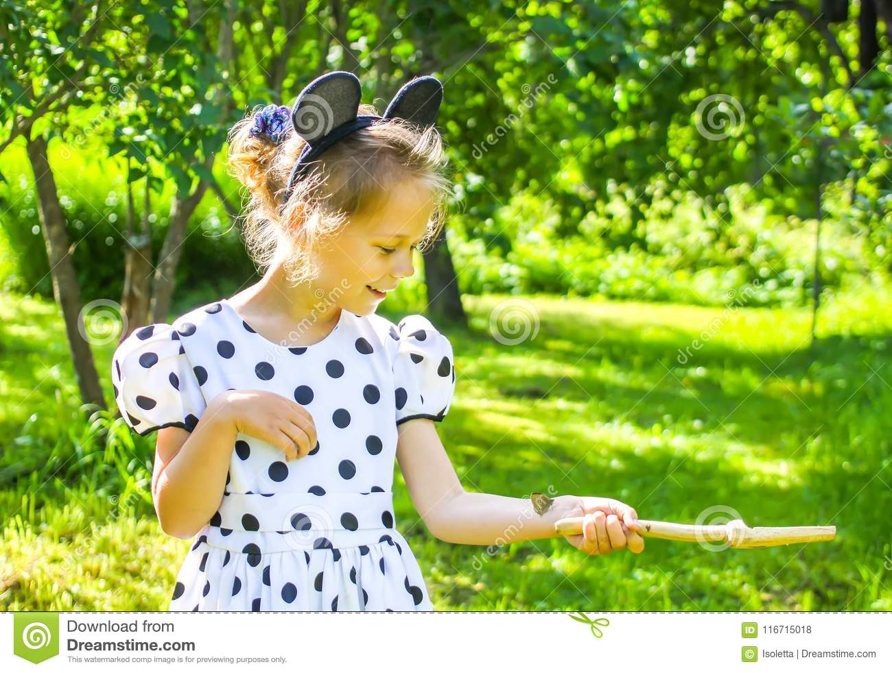 Little girl in summer park with small butterfly sitting on her hand