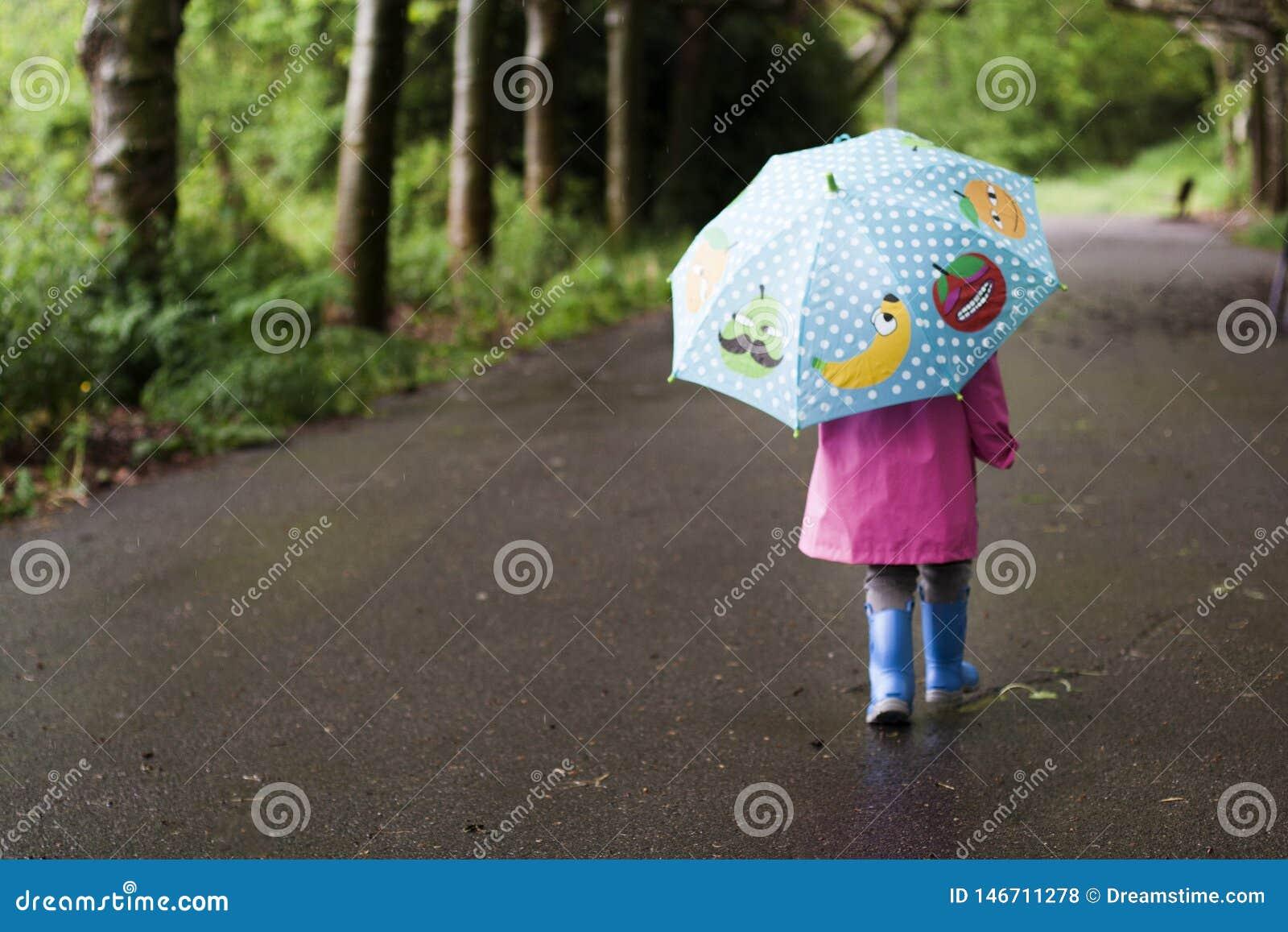 A little girl walks on a rainy day