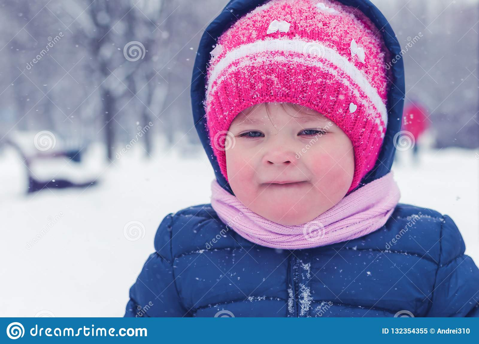 Little girl walks on the street in the winter day