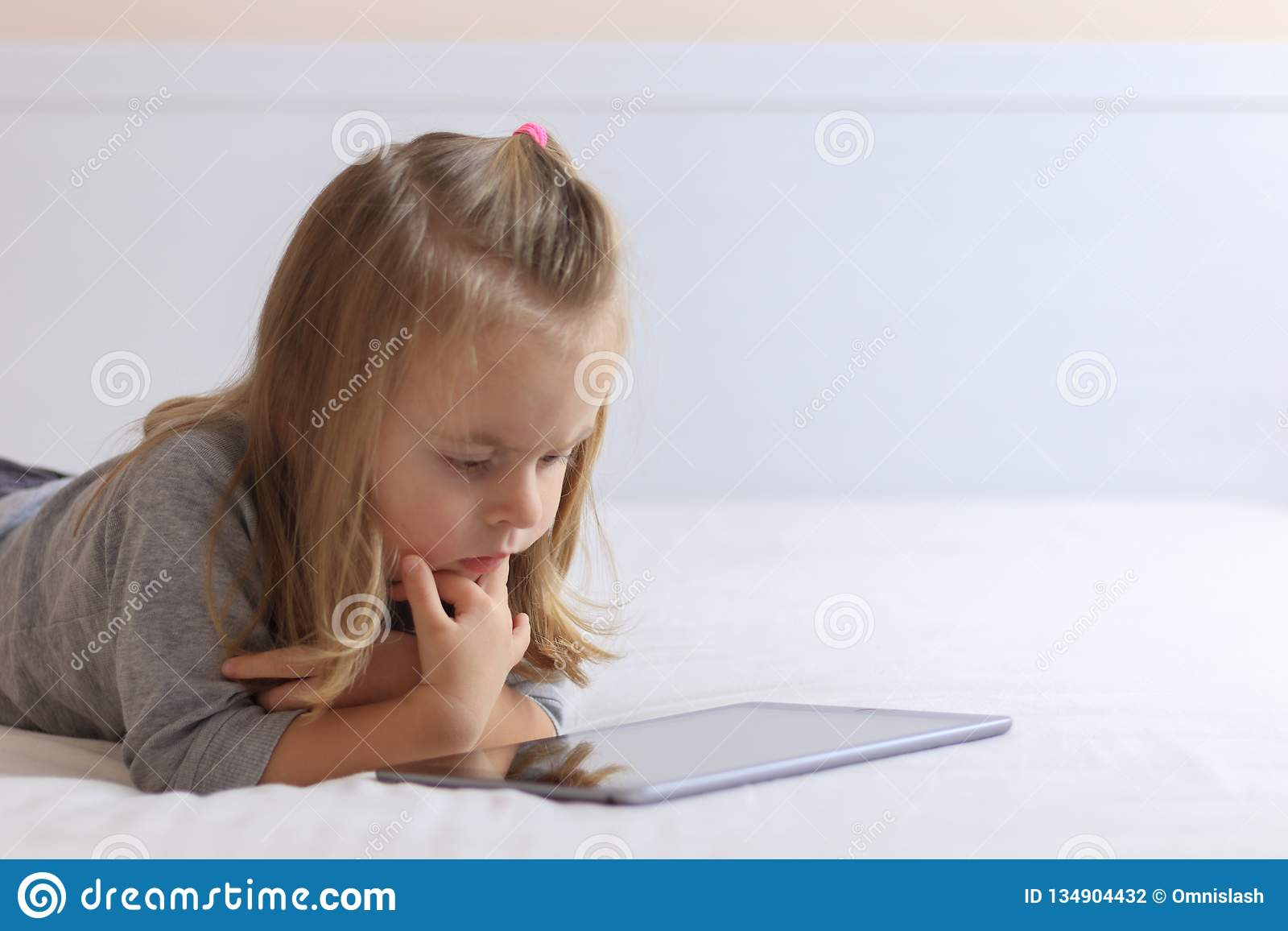 Little girl watching online streaming video while laying in bed