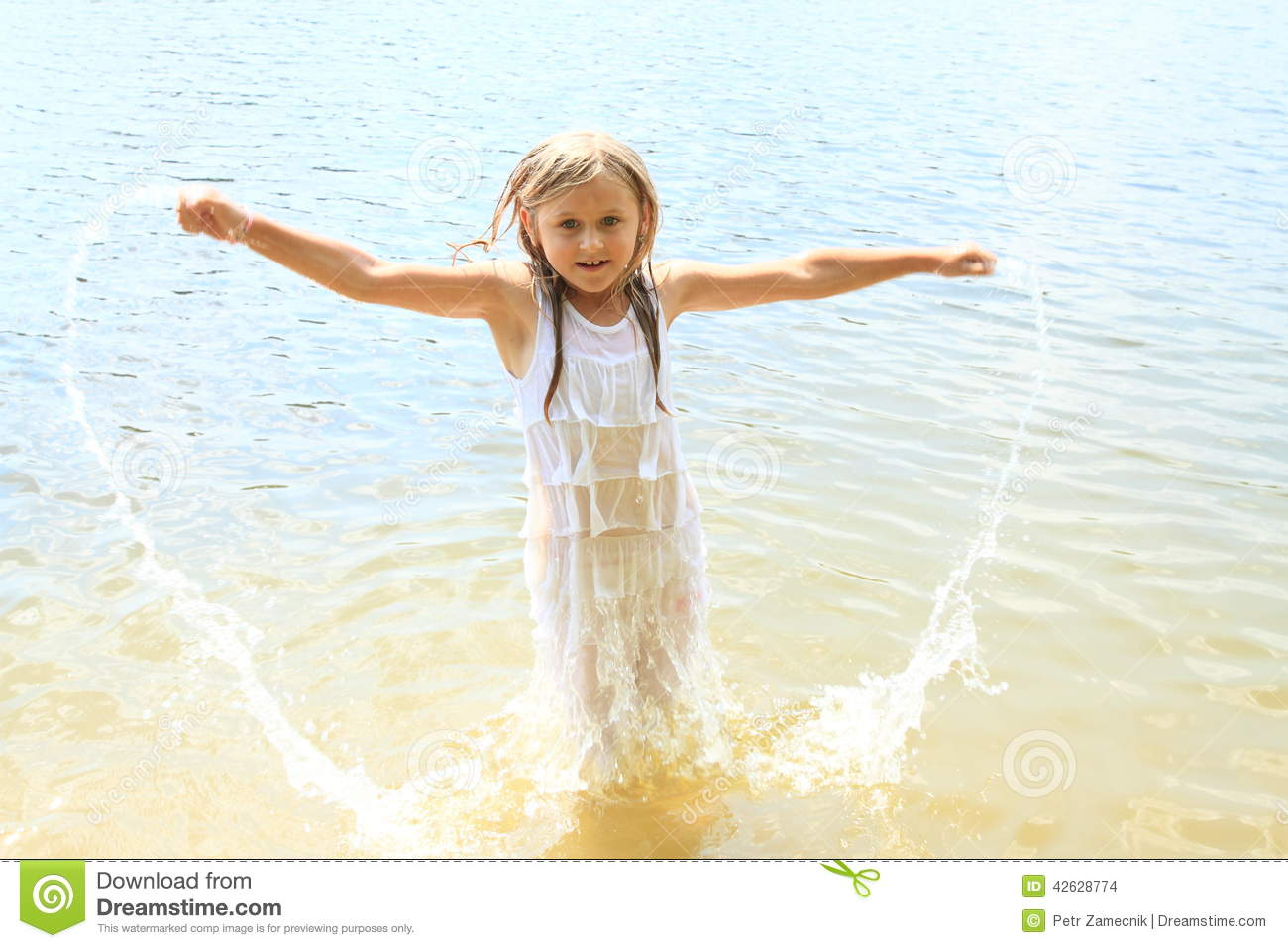 Little girl - kid in wet white clothes splashing the water.