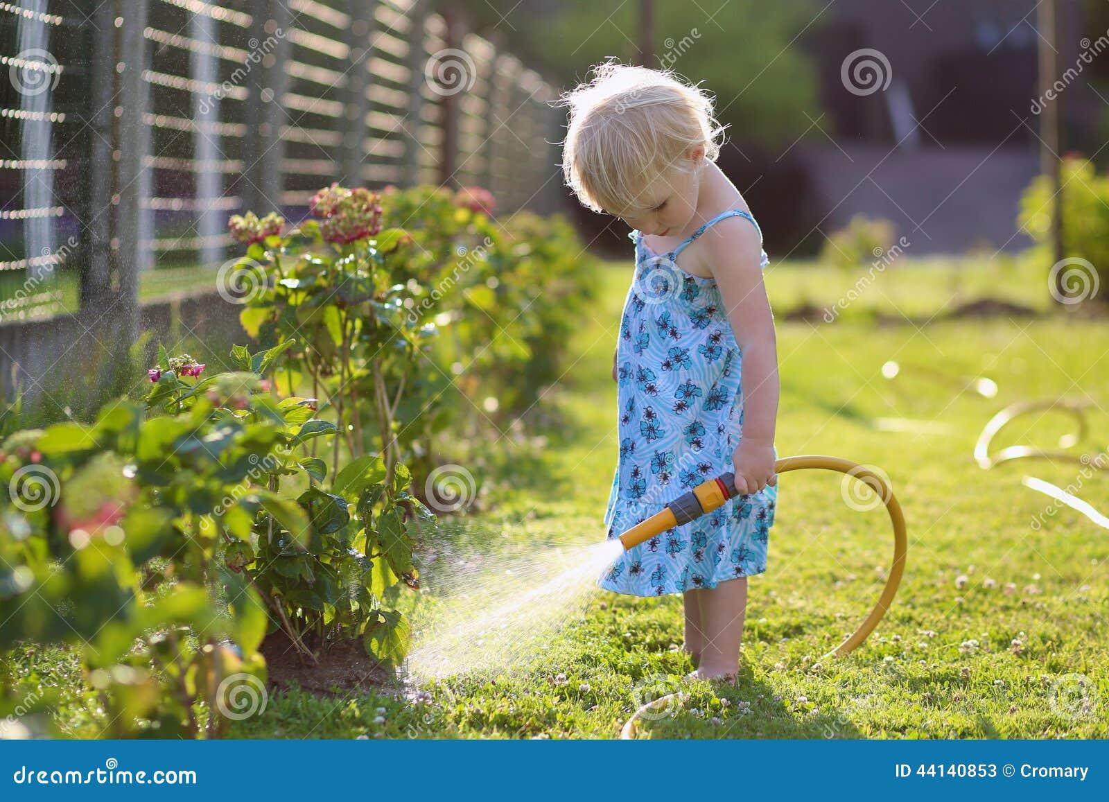 Backyard Garden Irrigation : Little girl watering plants in the garden stock photo