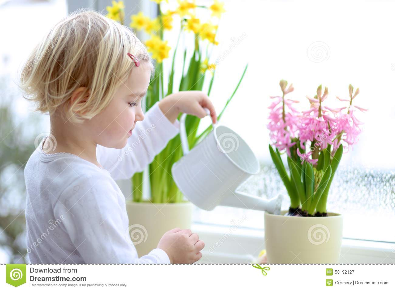 Little girl watering spring flowers at home