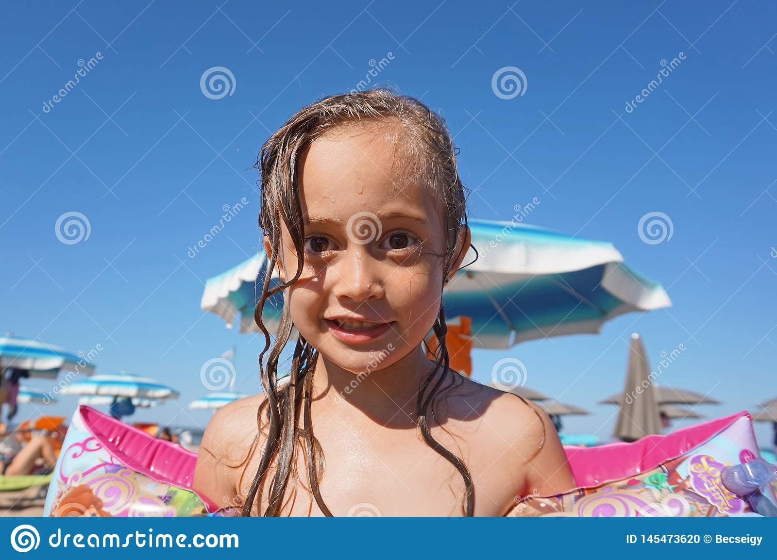 Little girl wearing arm floats on the beach