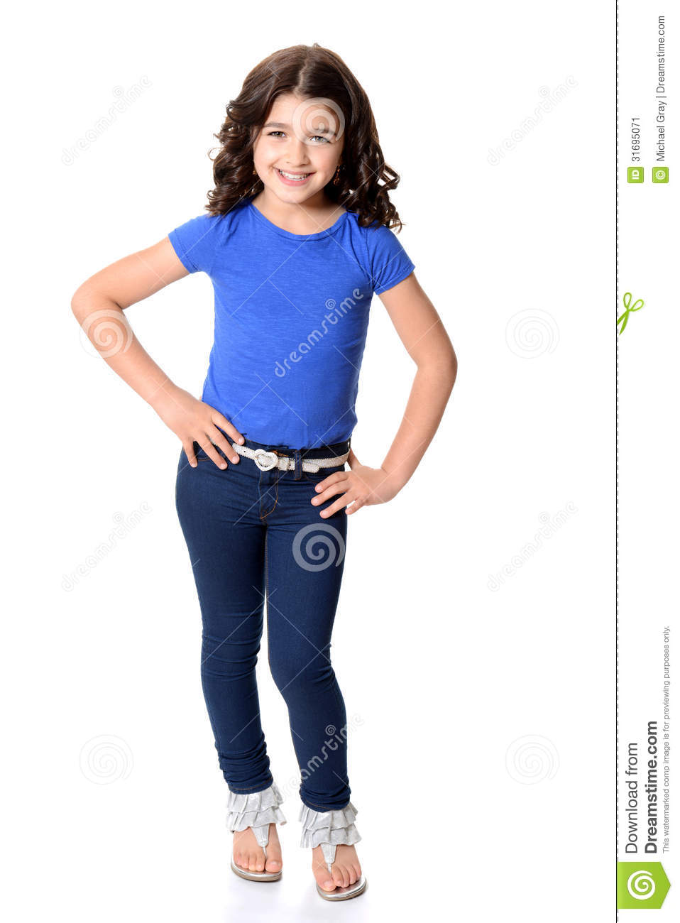 little girl wearing blue jeans with hands on hips stock