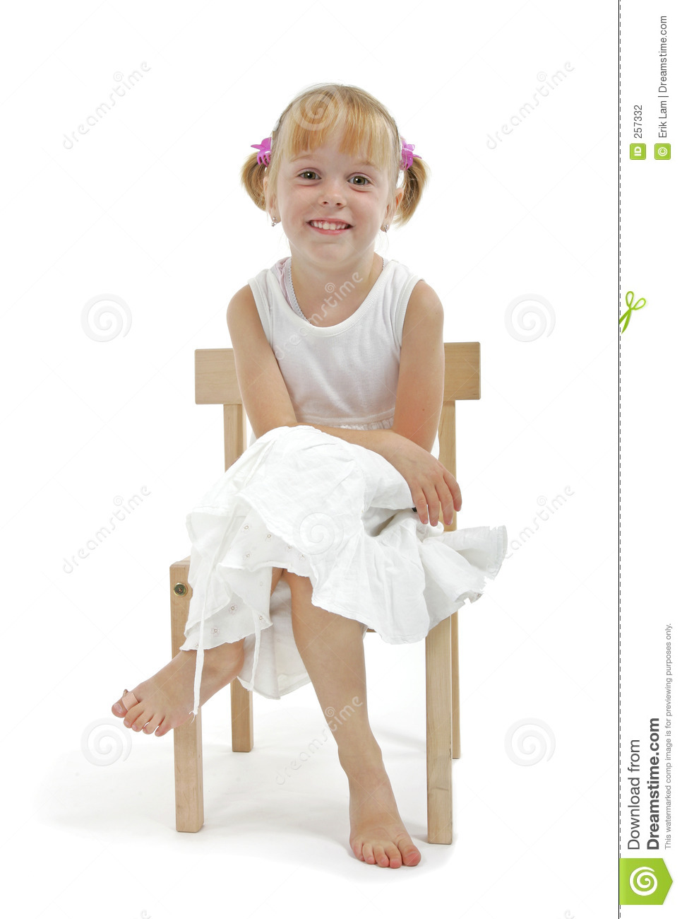 Little Girl In White Dress Sitting On Wooden Chair Stock