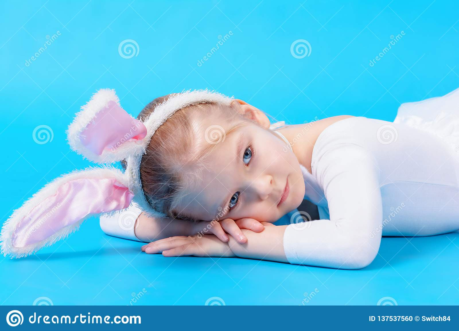 Little girl in a white rabbit costume on a blue background. The baby lies dreaming on the floor.