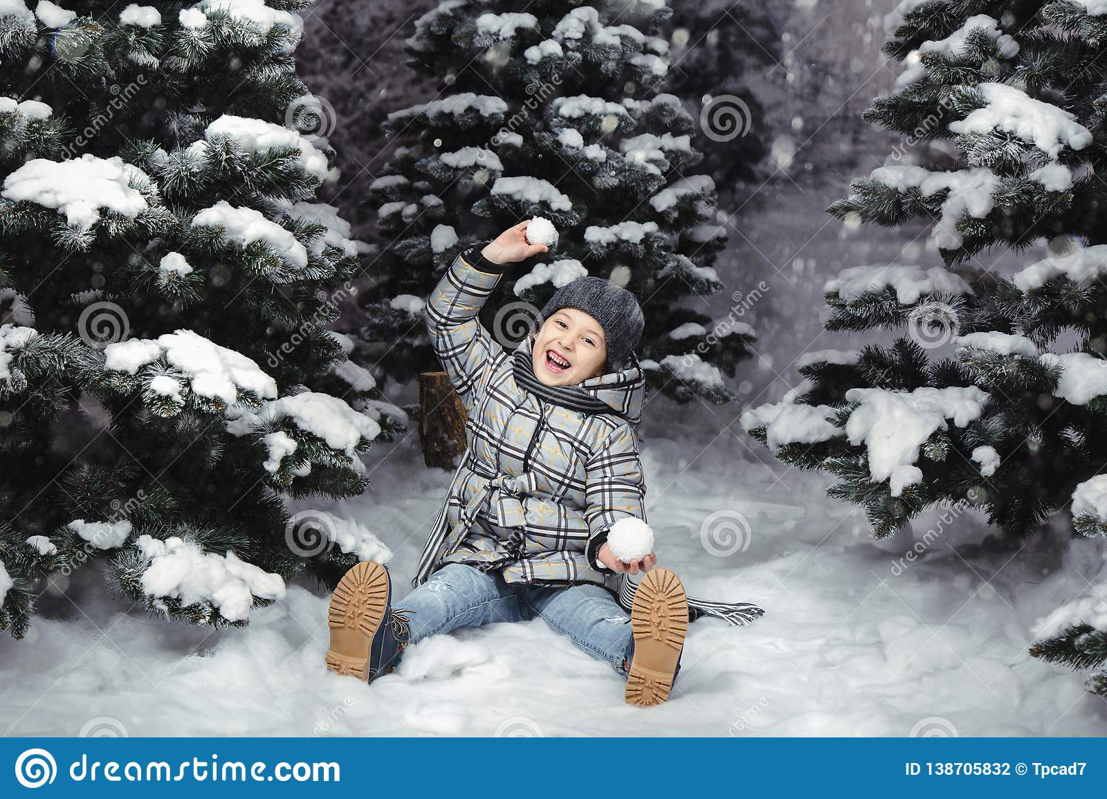 A little girl in winter clothes playing with snow on a snowy meadow surrounded by fir trees. Christmas concept. Studio