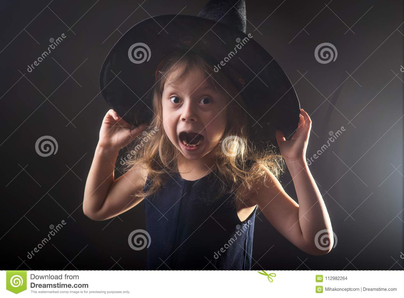 Little girl in witch hat on a dark background, banner for halloween.