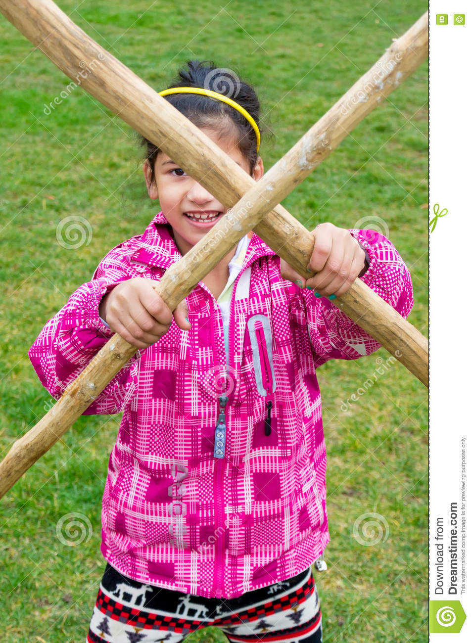 Little girl with wooden stick pole doing cross in fun fight