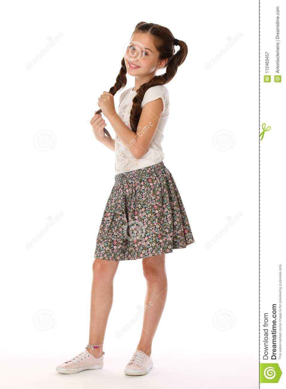 A little girl 12 years old posing in summer clothes. Charming pretty  slender young teenager is in a skirt with bare legs. Beautiful brunette  child is ...