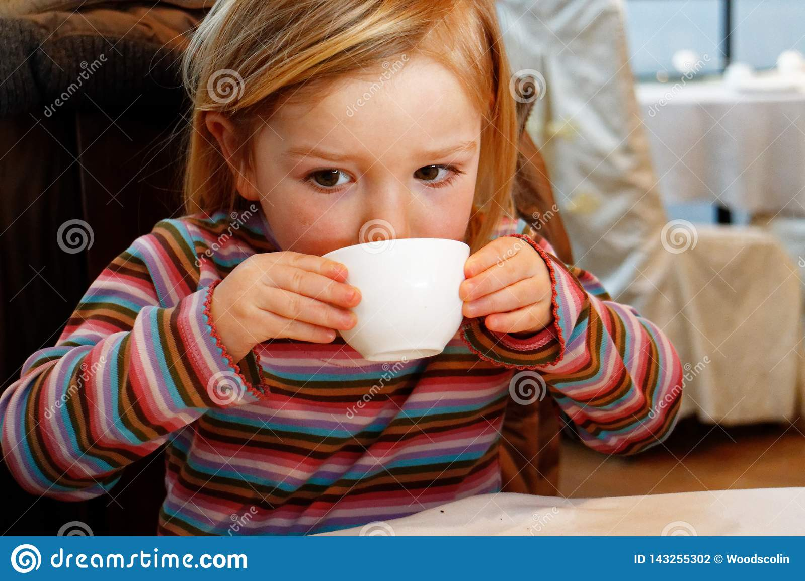A little girl drinking from a teacup