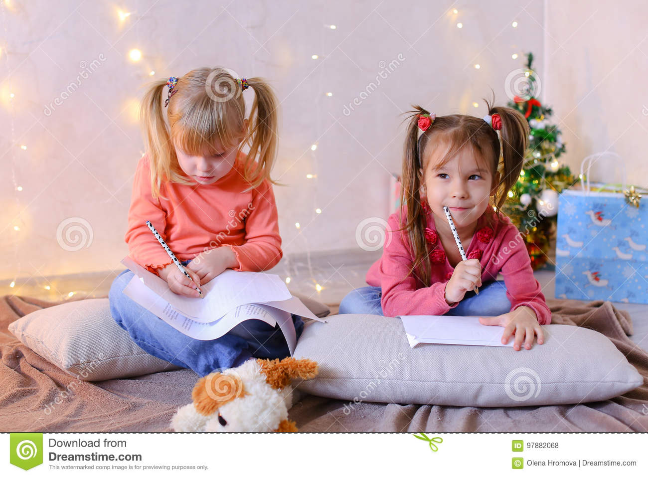 two lovely children of girls with smiles on their faces and in good spirits dream of new year gifts and write wishes for santa claus with pen on paper and