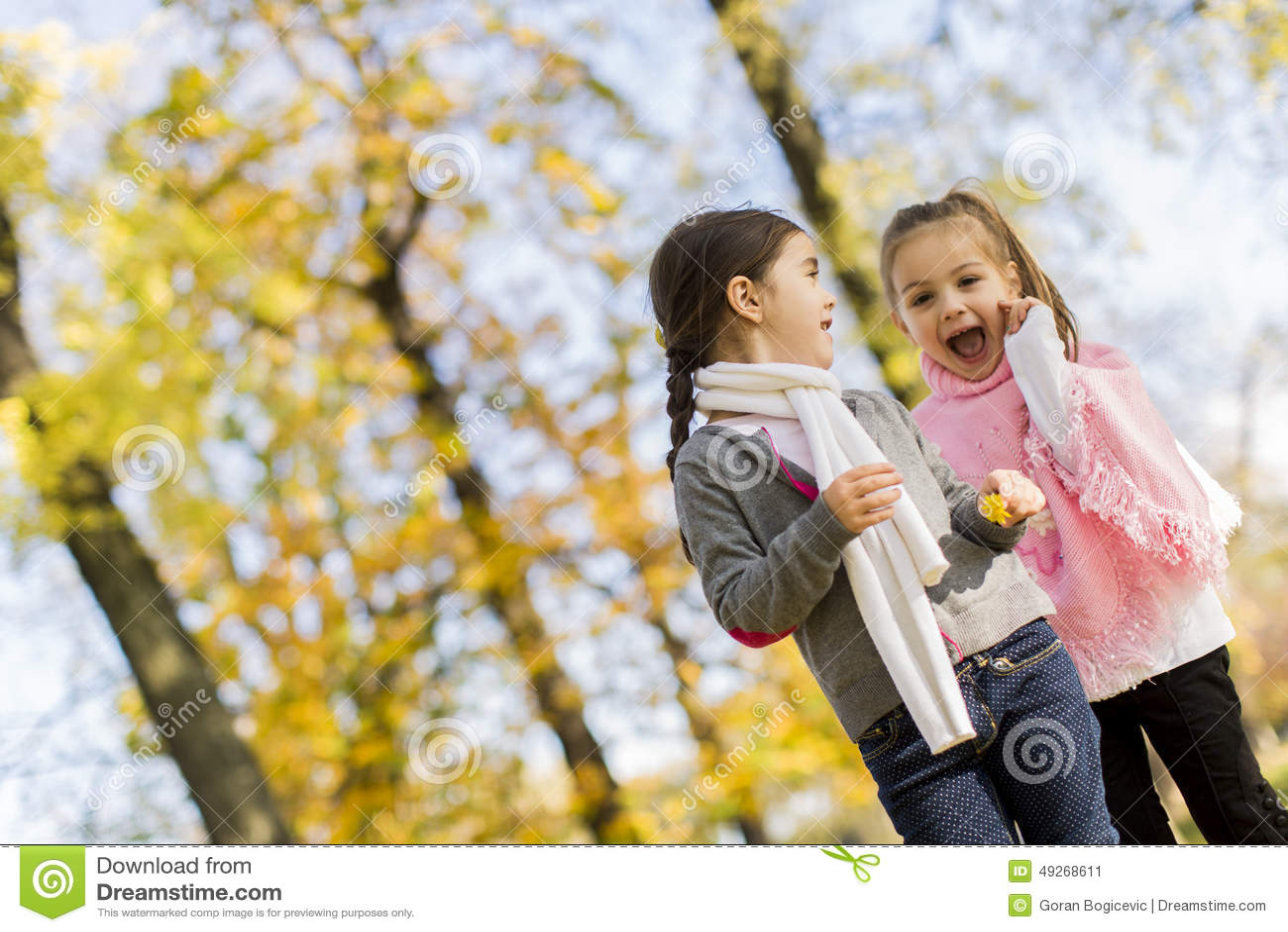 Little girls in the autumn park