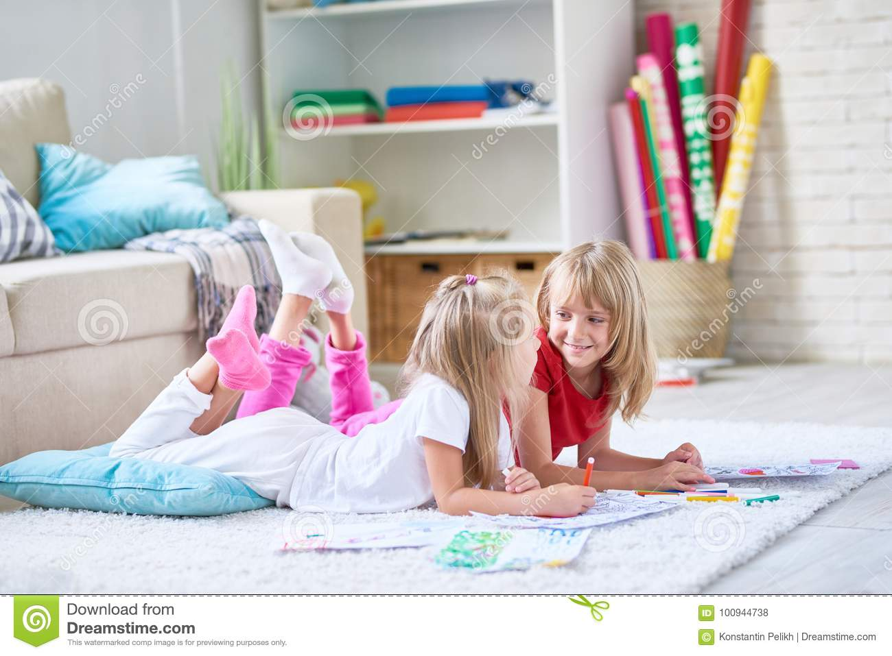 105db25dc64a1 Portrait of two happy little girls coloring pictures together lying on  floor on thick plush carpet in cozy living room at home