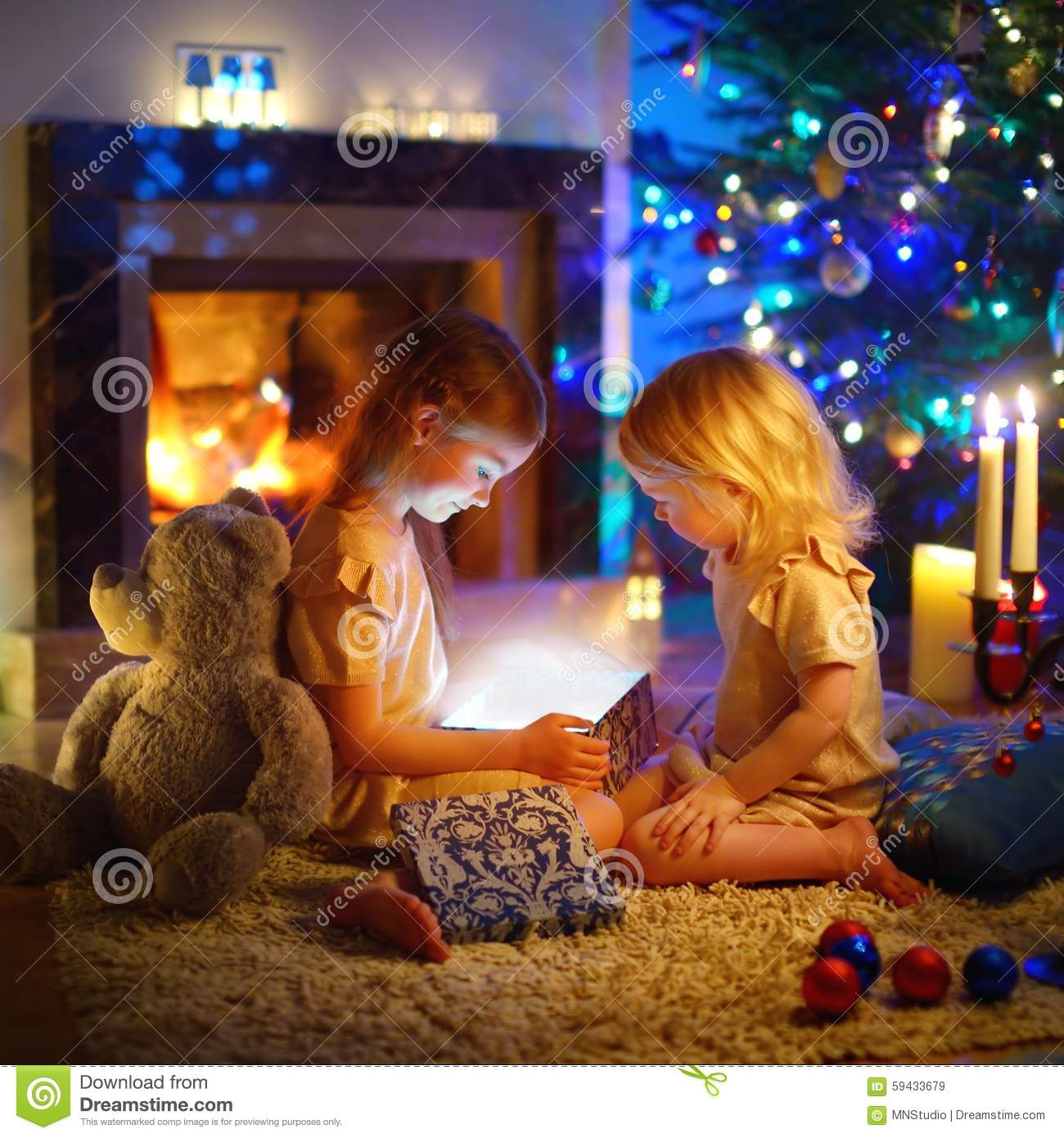 Little Girl Christmas Tree: Little Girls Opening A Magical Christmas Gift Stock Image