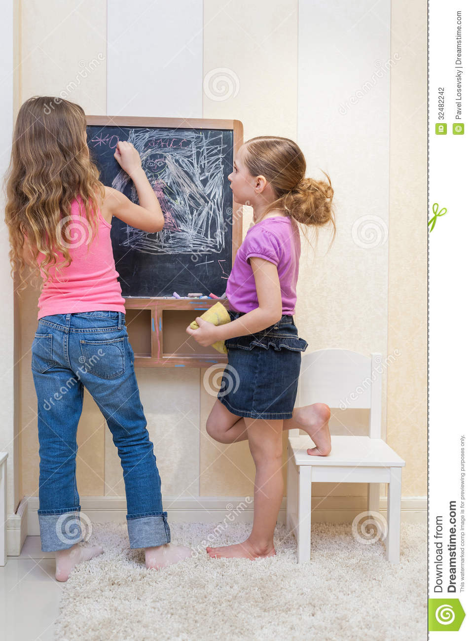 Little girls in the playroom paint on the blackboard