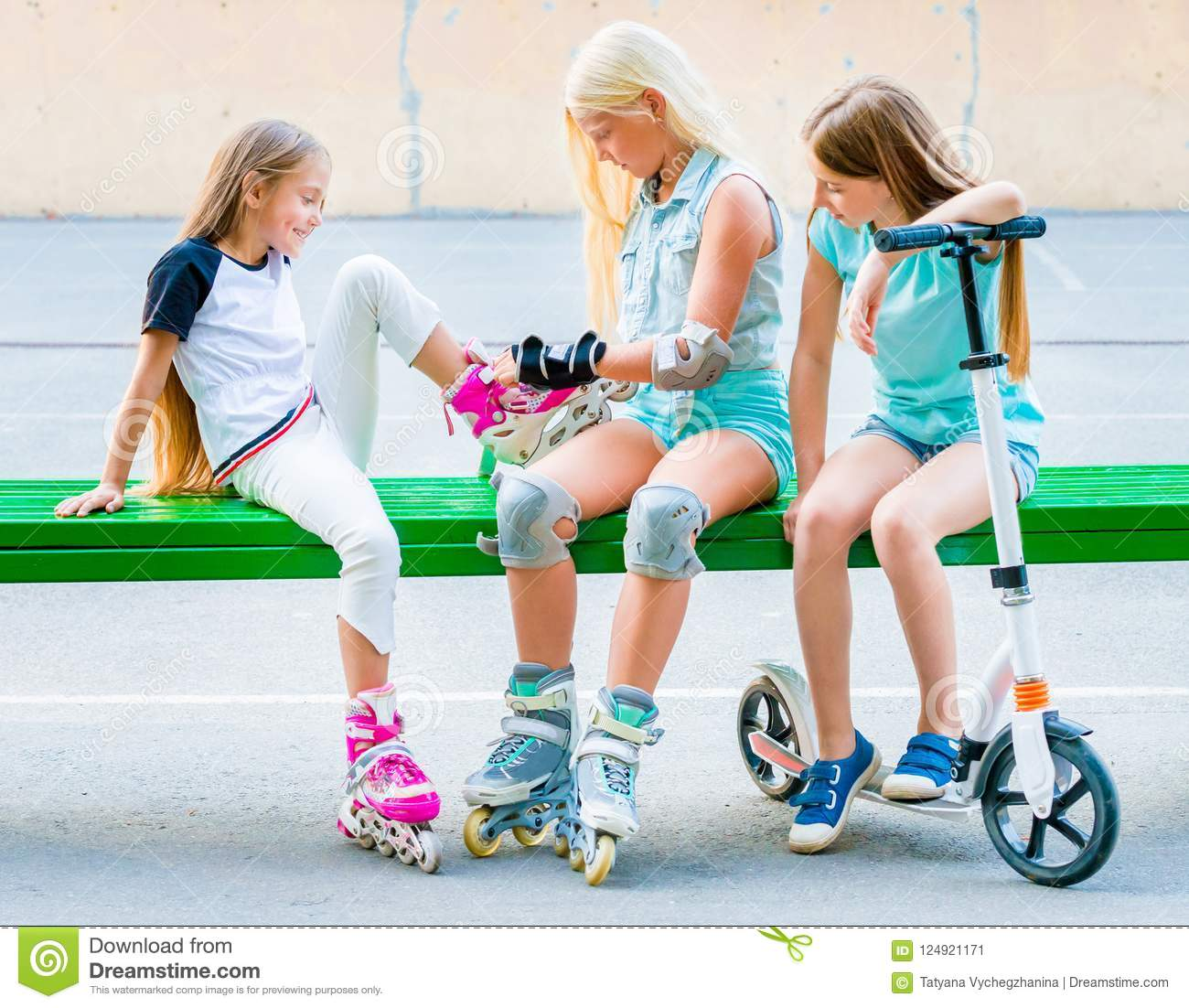 Little girls putting on rollerskates