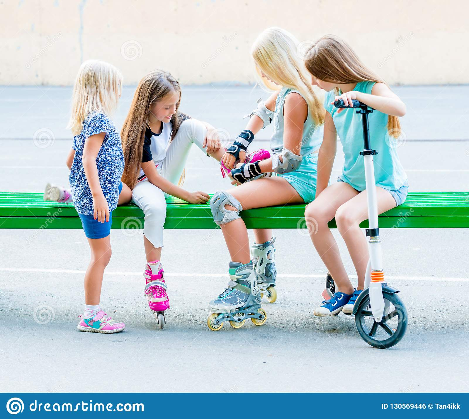 Little girls putting on rollerskates