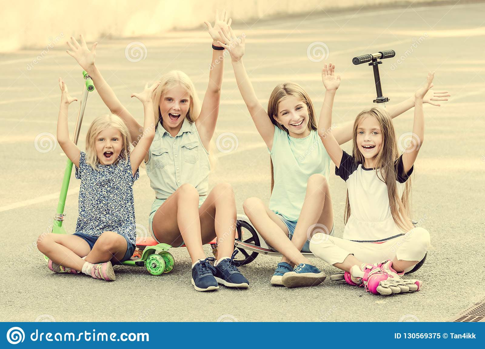 Little girls smiling sitting on the ground with raised hands