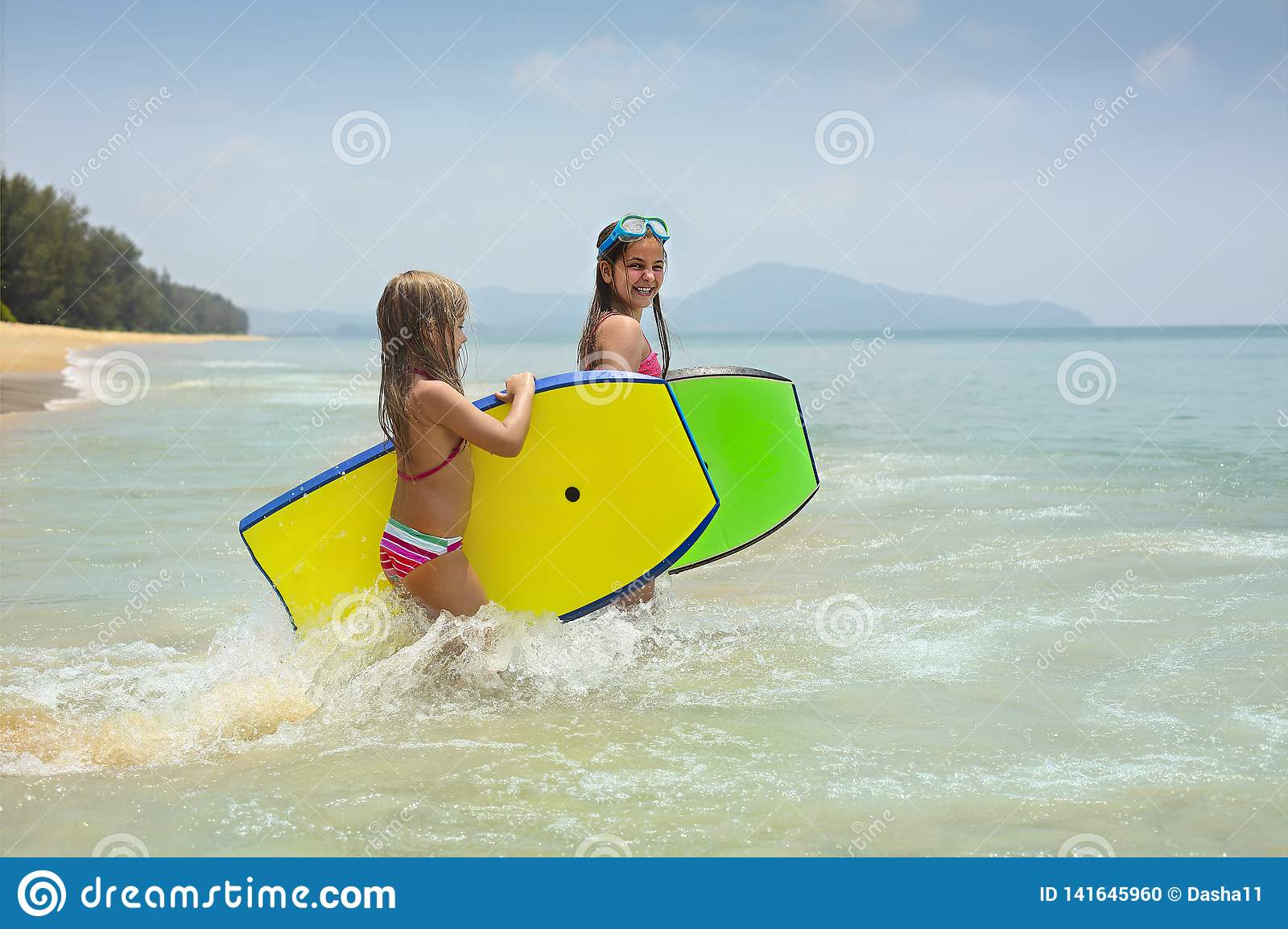 Little girls with surfing boards playing on tropical ocean beach. Summer water fun for surfer kids