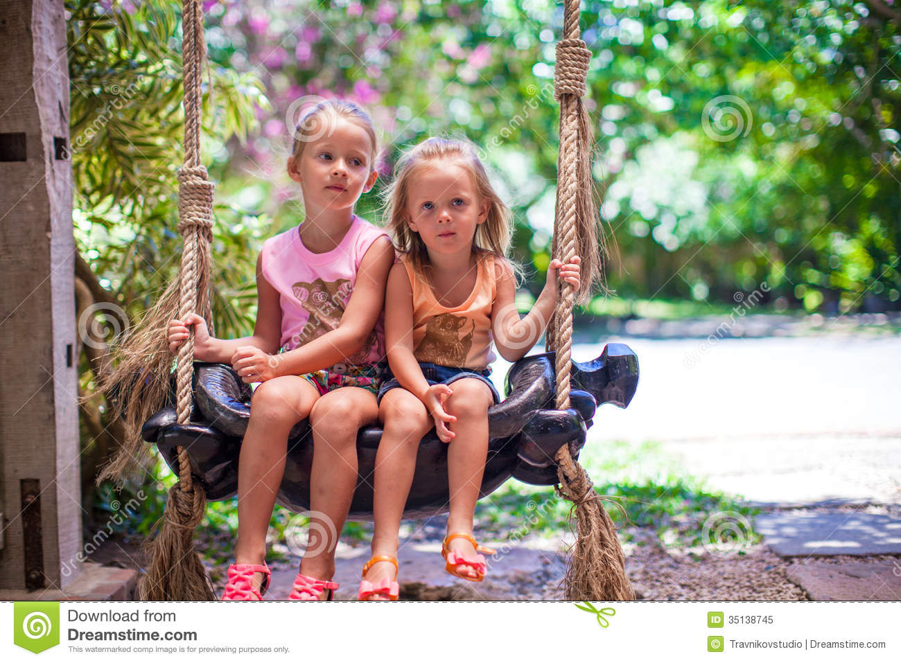 Little Girls Swinging In A Cozy Lovely Flowered Royalty Free Stock ...