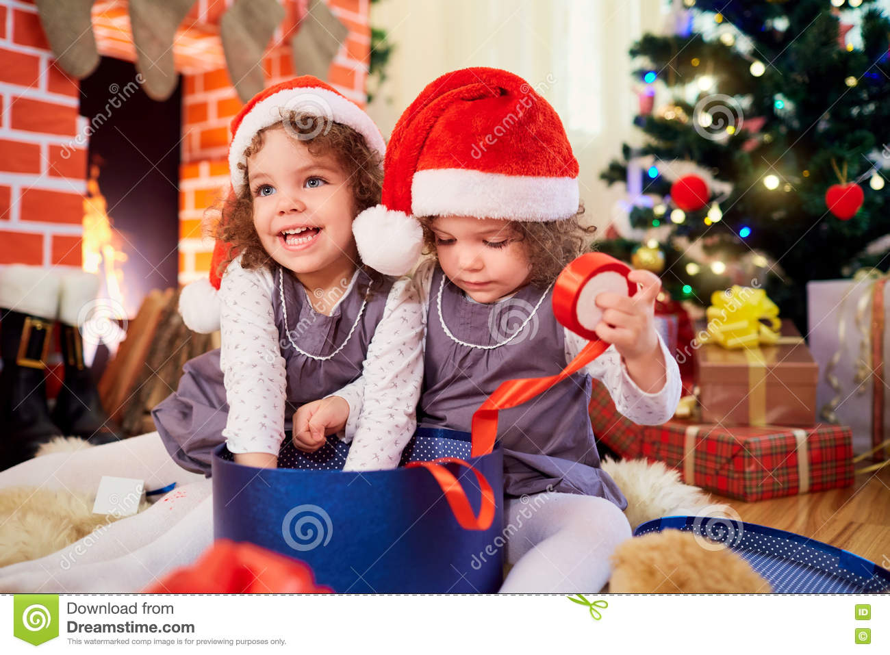 f84babd6a Little Girls Twins At Christmas Sitting On The Floor In Santa Ha ...