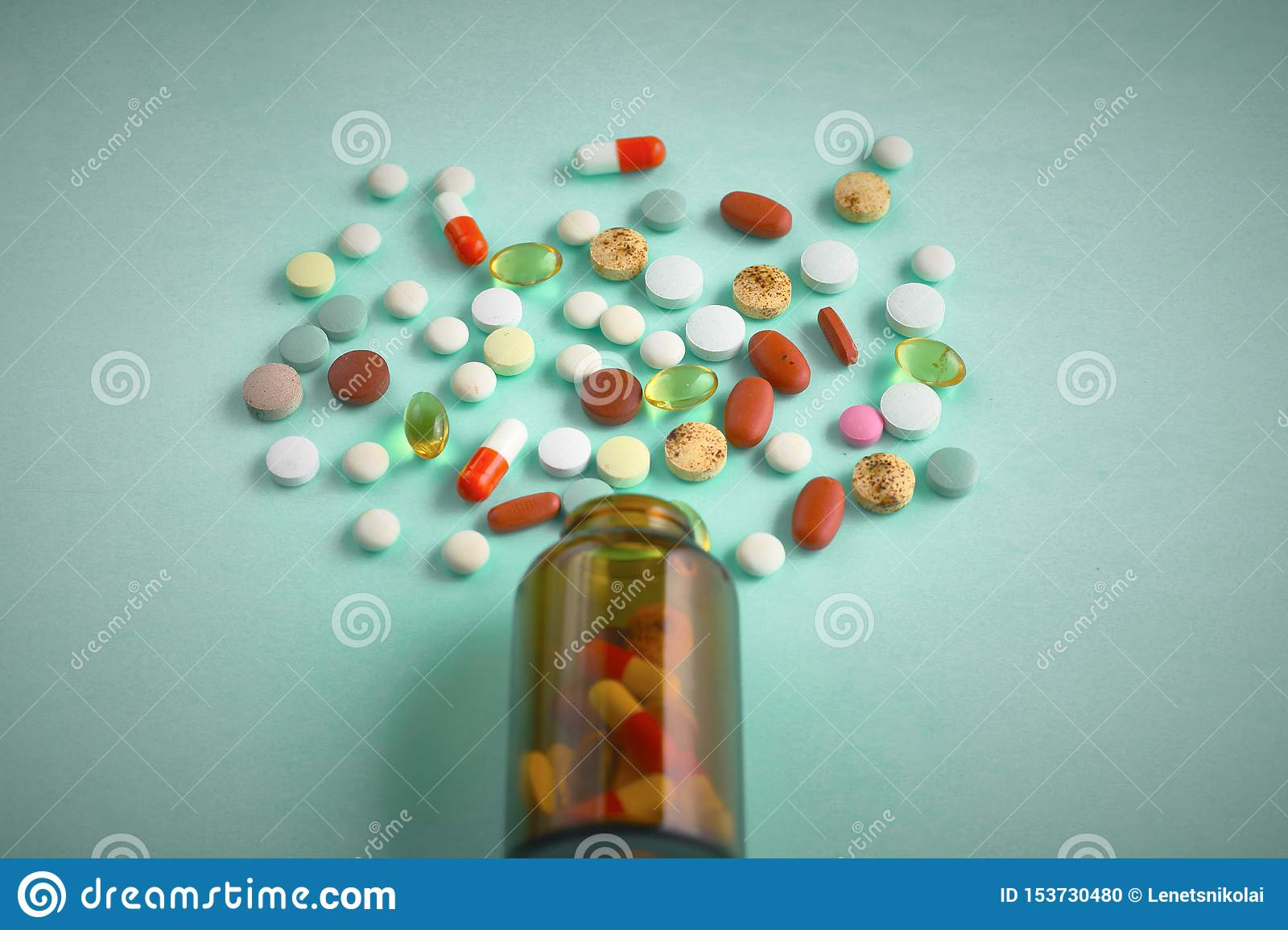 Little glass bottle with pills spilled over a table