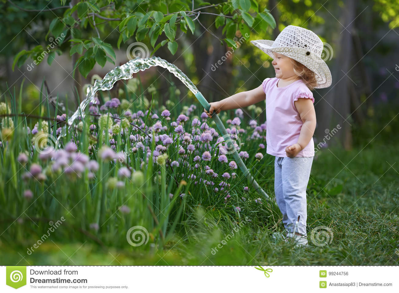 Little happy gardener watering onions