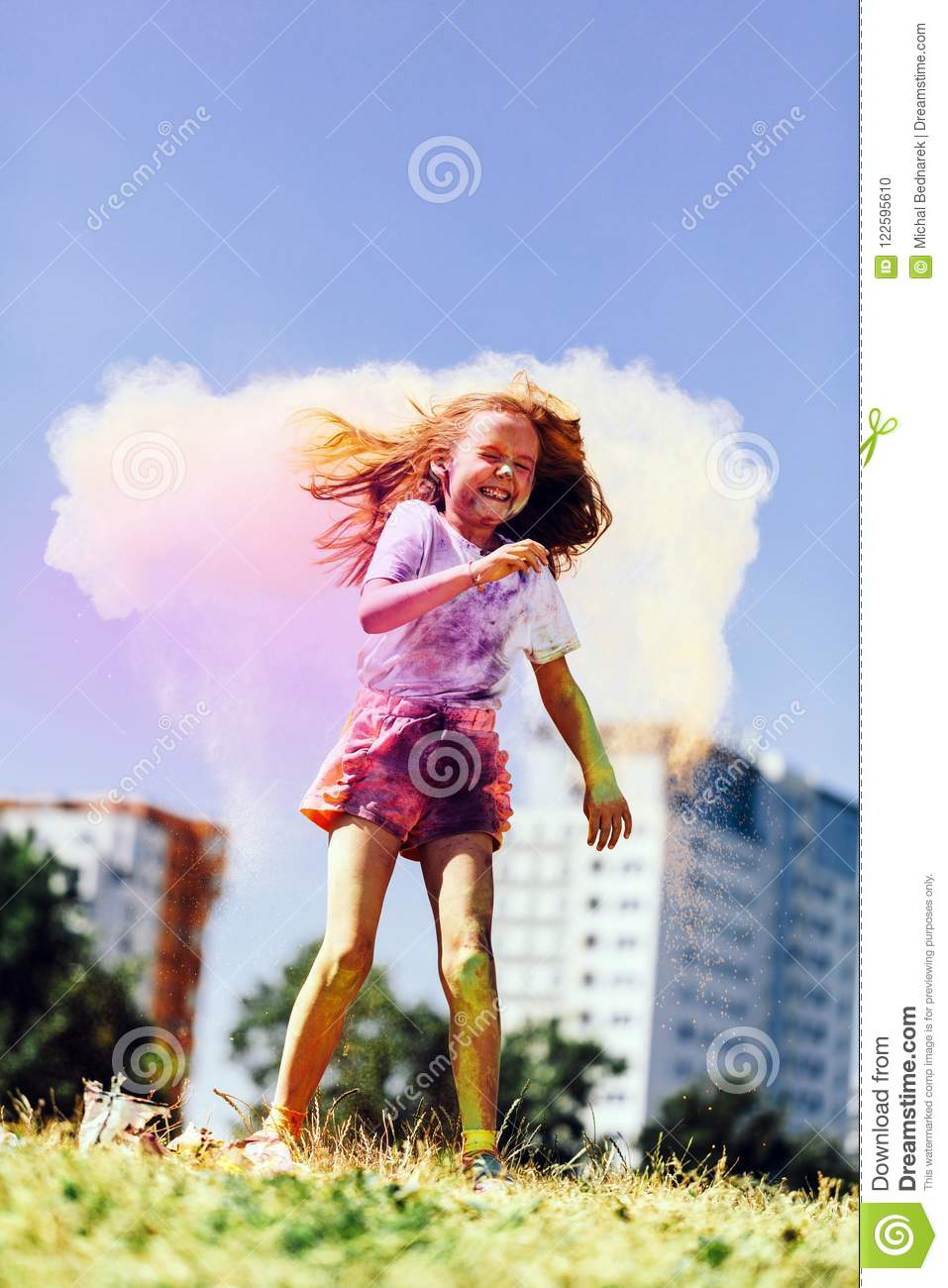 Little happy girl playing with colorful holi powder