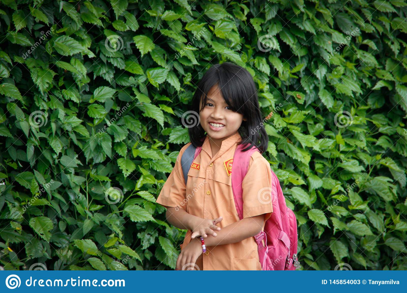 Little Indonesian schoolgirl walks with a school bag against a background of a wall with plants