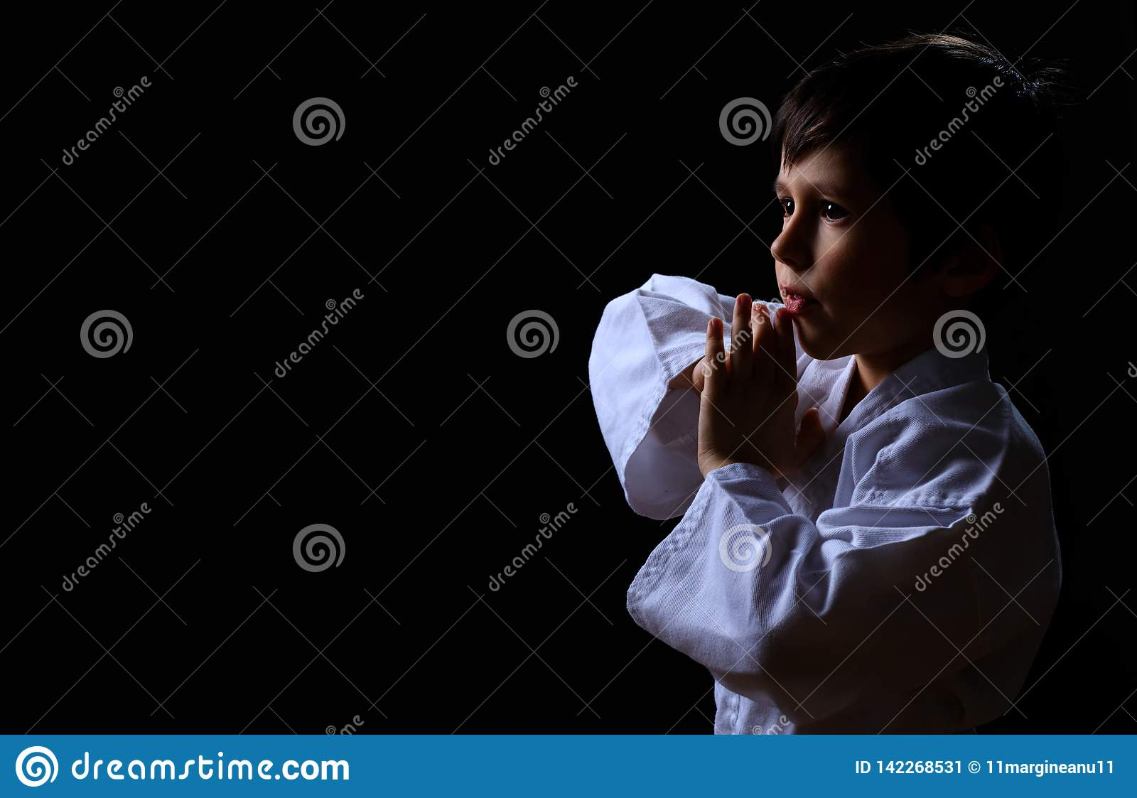 Little karate kid in white kimono isolated on dark background. Portrait of boy ready for martial arts fight. Child fighting at