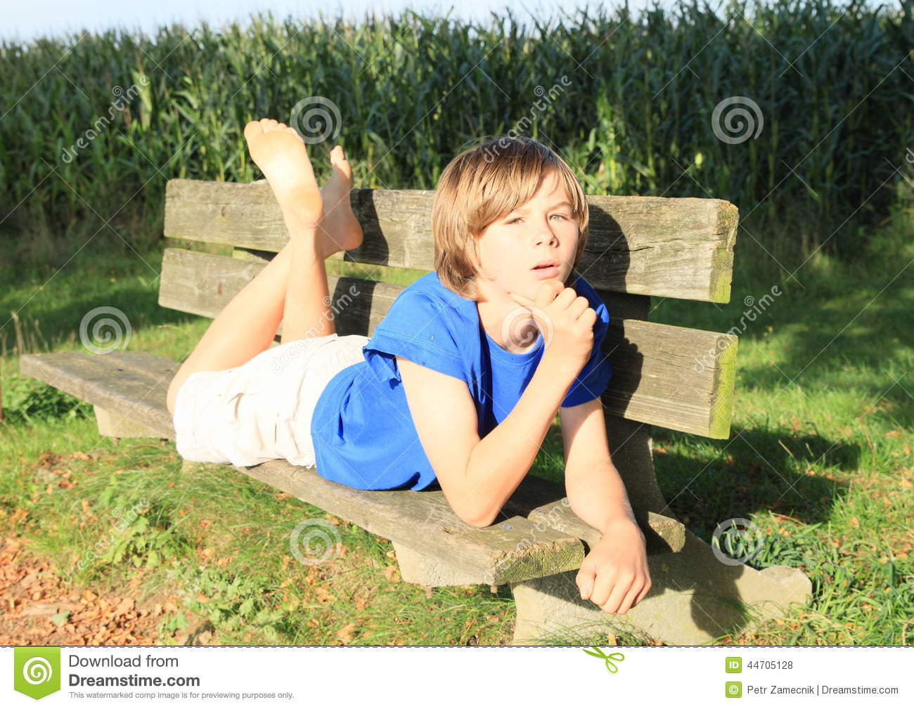 ... kid - barefoot boy lying on wooden bench with corn field behind
