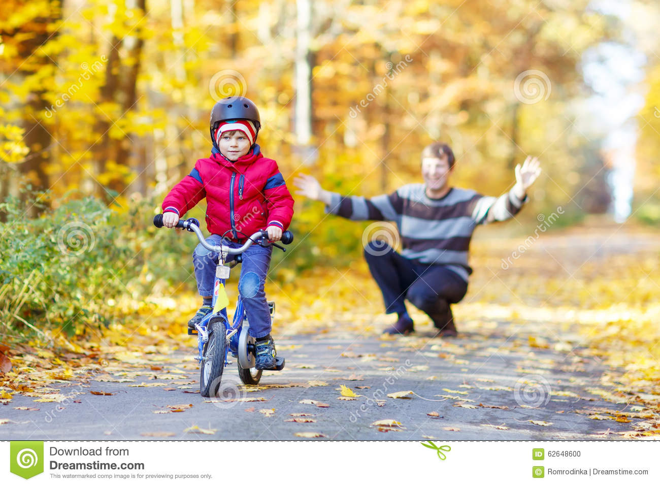 Little kid boy and father with bicycle in autumn