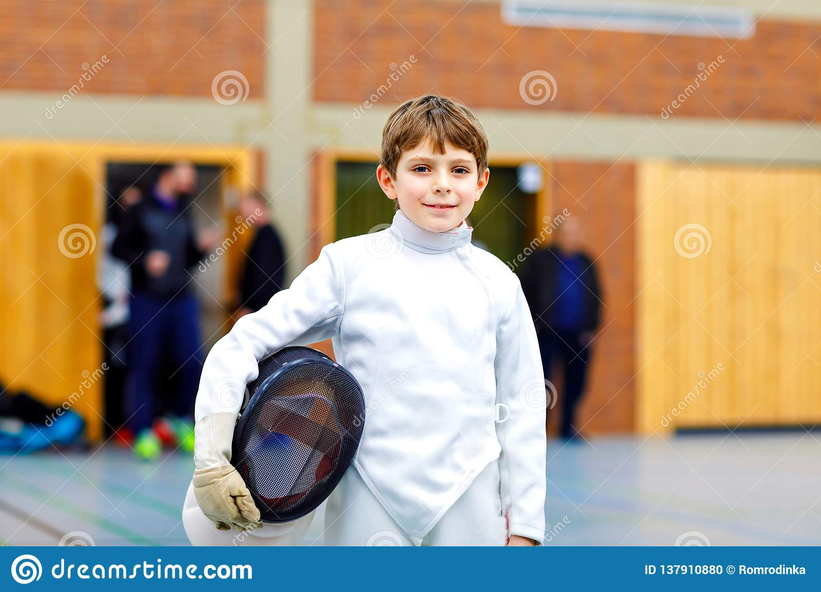 Little kid boy fencing on a fence competition. Child in white fencer uniform with mask and sabre. Active kid training