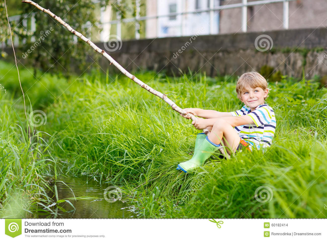 Little kid boy fishing on river with selfmade fishing rod for Little kid fishing pole