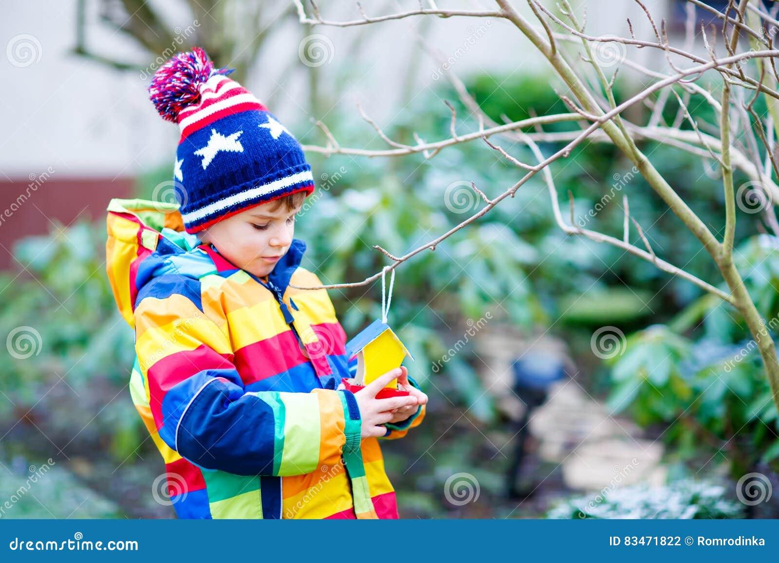 Groovy Little Kid Boy Hanging Bird House On Tree For Feeding In Download Free Architecture Designs Scobabritishbridgeorg