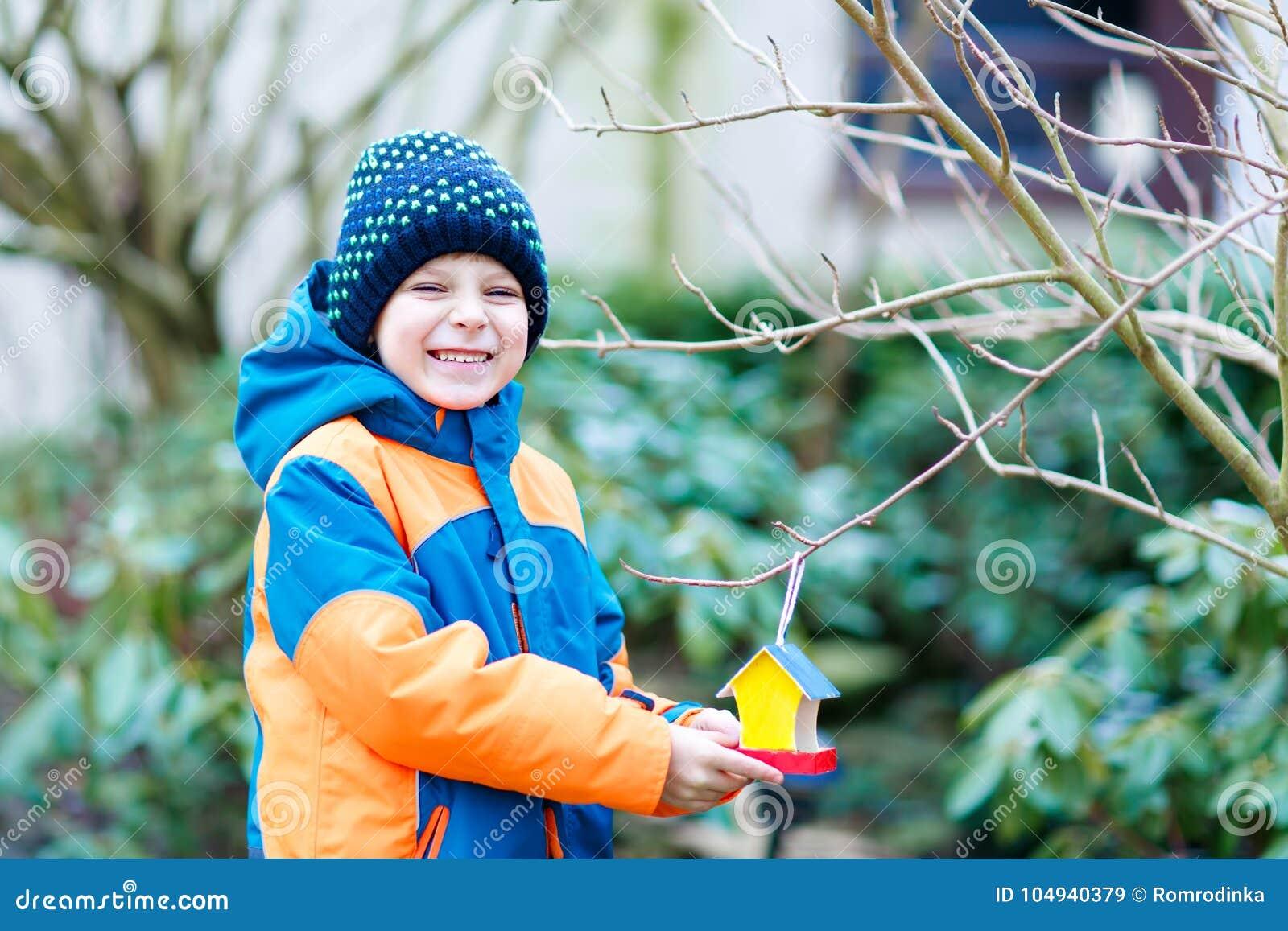 Magnificent Little Kid Boy Hanging Bird House On Tree For Feeding In Download Free Architecture Designs Scobabritishbridgeorg