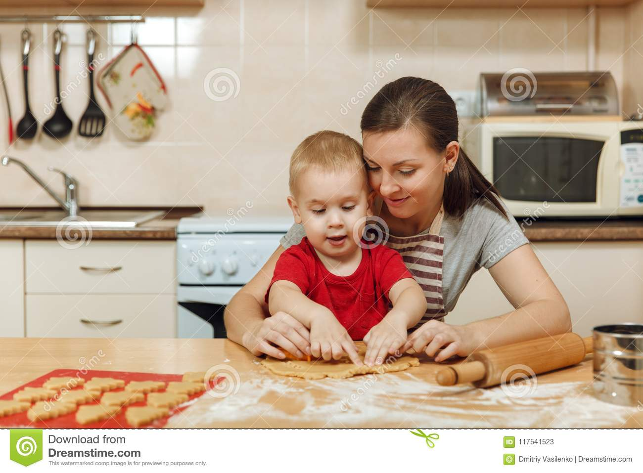 Little kid boy helps mother to cook ginger biscuit. Happy family mom and child in weekend morning at home. Relationship.